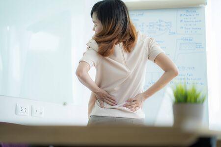 Asian woman with back pain in office Foto de archivo
