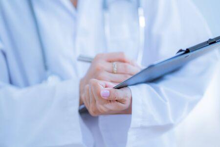 Close-up view of female doctor hands filling patient registration form. Healthcare and medical concept Banco de Imagens