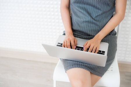 Portrait of young woman working and using laptop.