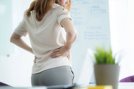 Asian woman with back pain in office Banco de Imagens
