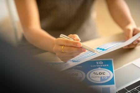 Mujer de negocios asiática revisando datos en cuadros y gráficos financieros. Contabilidad Foto de archivo
