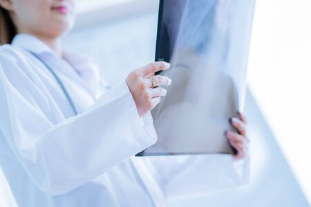 Asia Woman Doctor Looking at X-Ray Radiography in patients Room Stock Photo