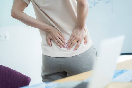Asian woman with back pain in office Stock Photo