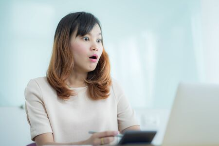 Asian businesswoman laughing with joy at workplace, gladly looking at laptop screen, feeling excited about online win, watching funny video on computer, enjoying positive good news in internet