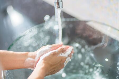 Washing hands with soap under the faucet with water 写真素材