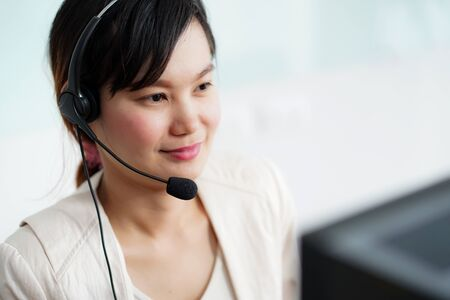 Portrait of happy smiling female customer support phone operator at workplace. Asian Foto de archivo