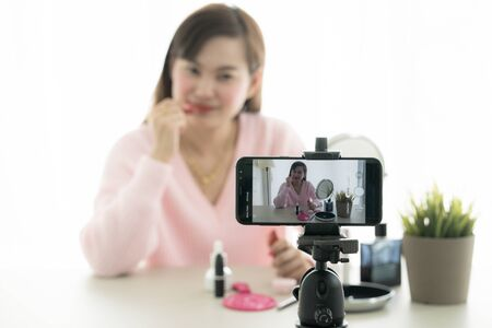 Asian blogger live broadcasting cosmetic makeup tutorial viral video clip Stock Photo