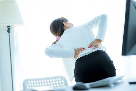 Asian woman with back pain in office Standard-Bild