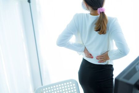 Asian woman with back pain in office Stock fotó