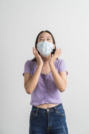 Close up portrait of young woman with medicine health care mask against white white background. CoronaVirus, Covid-19. Asian people