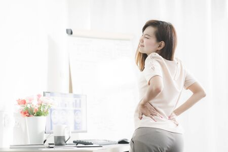 Business woman with back pain in office. Asian people. Work at home concept
