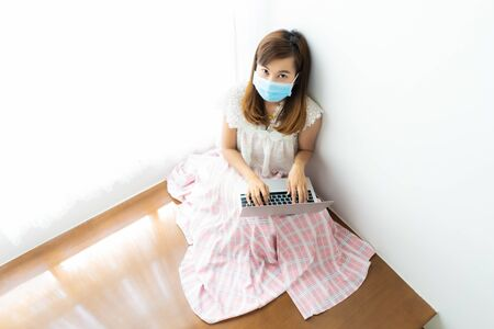 Asian woman working or learn from home with laptop and medicine health care mask on stair