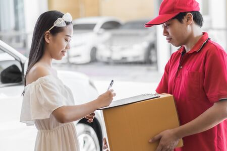 Asian woman receiving a package at home from a delivery guy