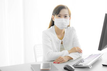 Asian woman using the medical face mask in office