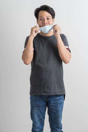 Portrait of young man with medicine health care mask against white gray background. Asian people