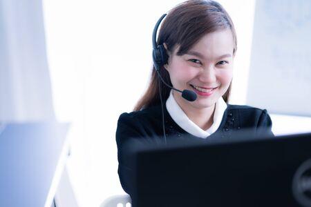 Asiatische junge Frau, die im Callcenter arbeitet