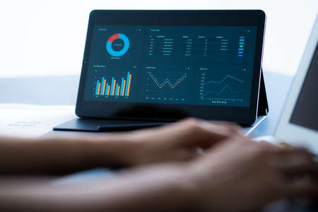 Asian business woman reviewing data in financial charts and graphs with tablet. Accounting