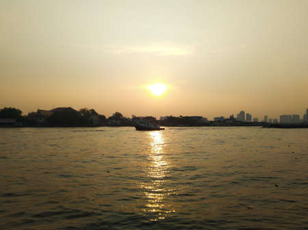 The beauty of the orange light of the sunrise on the water surface, blurred view dark background.