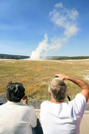 a couple watching a geyser eruption from a distance