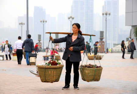 Chongqing, China, March 18, 2012 - A Chinese woman carrying vegetables in chests in Chongqing.