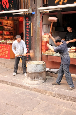 hammering: Chongqing, China, March 19, 2012 - Two Chinese men hammering ginger dough in the process of making sweets.