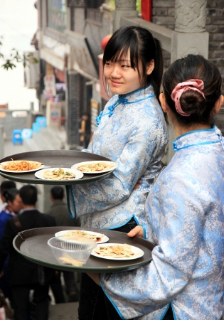 Chongqing, China, March 19, 2012 - Two Chinese servers carrying food in Chongqing Stock Photo - 14148677