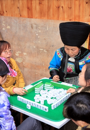 Fenghuang, China, March 23, 2012 - People playing mahjong in a street of Fenghuang