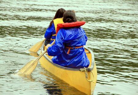 Parry Sound, Canada, August 12, 2012 - Two women paddling on a canoe