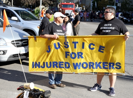 Toronto, Canada, September 3, 2012 - A banner supporting justice for injured workers at the 2012 Toronto Labor Day Parade Stock Photo - 15240210