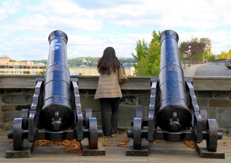 Quebec City, Canada, September 9, 2012 - A woman between two cannons in the old part of Quebec City Stock Photo - 15838428