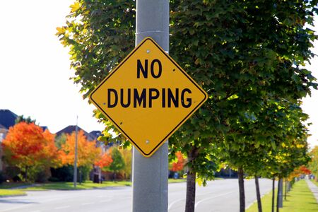 dumping: A yellow No Dumping sign in Canada