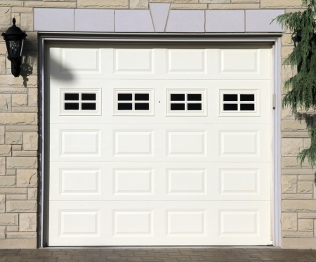 A white garage door of a detached house