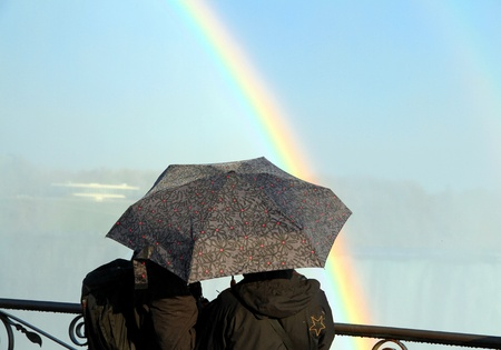 A couple with an umbrella and a rainbow
