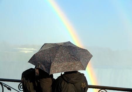 lluvia paraguas: Una pareja con un paraguas y un arco iris