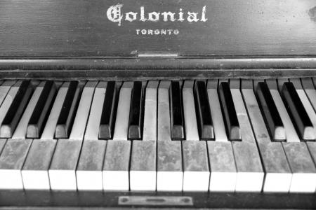 TORONTO - APRIL 9: An old Colonial piano on April 9, 2013 in Toronto. An old company manufacturing piano, Colonial Piano Co was from Ste-Therese, Quebec and operated until the 1920s.