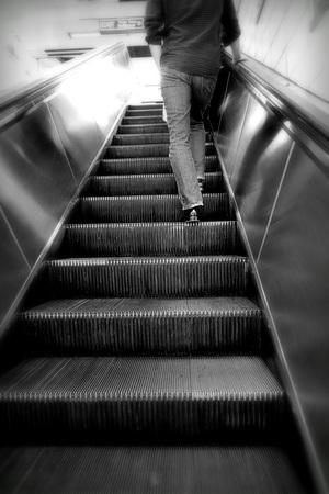 Man walking up an escalator