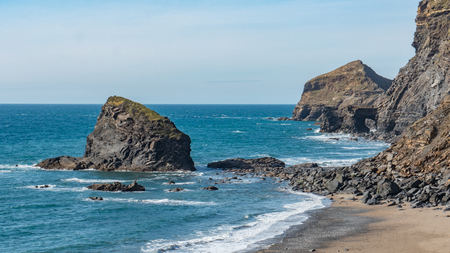 south west england: A rural rocky beach located in amongst of the cliffs of Cornwall, England.