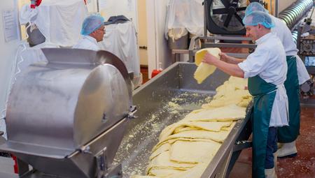 Men traitement fromage à l'intérieur d'une usine utilisant un broyeur dans lequel ils déchiquettent des blocs de fromage pour l'emballage Banque d'images - 58798428