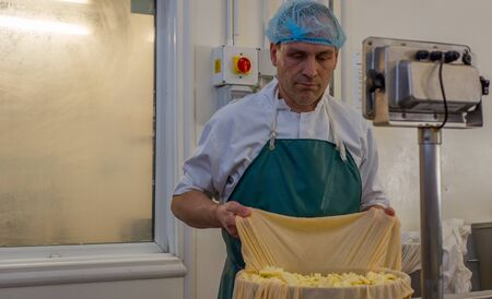 Man packs Cheese into a metal tub for pressing, taken in a Cheese factory