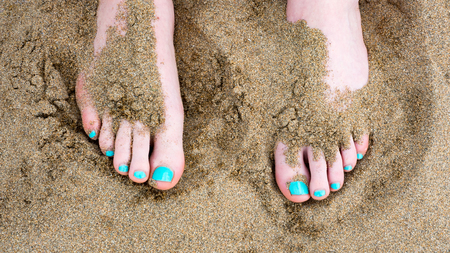 painted toes: Toes against sand at the beach with painted nails Stock Photo