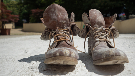 Old brown work boots covered in concrete