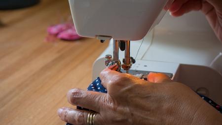 Weibliche Hand mit Nähmaschine Nähte fabic Standard-Bild - 80864828
