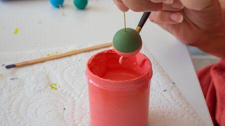 Weibliche Hände Malerei Polymer Lehm. Handgefertigte Werkstatt Zusammensetzung aus Ton, Perlen, Werkzeuge und Farbe Standard-Bild - 80844894