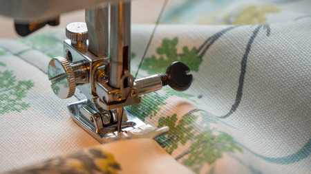 female hand using sewing machine stitching fabic