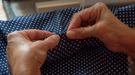 female hands pinning and stitching fabic