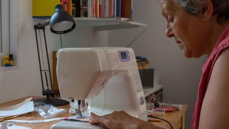 elderly woman using sewing machine stitching fabic