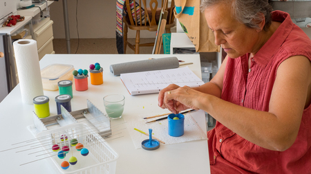 woman painting polymer clay beads. Handmade workshop composition of clay, beads, tools and paint