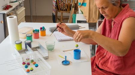 Frau, die Polymer-Lehmperlen malt. Handgemachte Werkstattzusammensetzung von Lehm, Perlen, Werkzeugen und Farbe Standard-Bild - 80864877