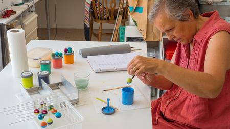 Frau, die Polymer-Lehmperlen malt. Handgemachte Werkstattzusammensetzung von Lehm, Perlen, Werkzeugen und Farbe Standard-Bild - 80812804