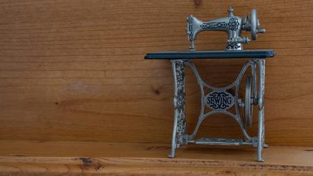 minature sewing machine against wooden background Standard-Bild